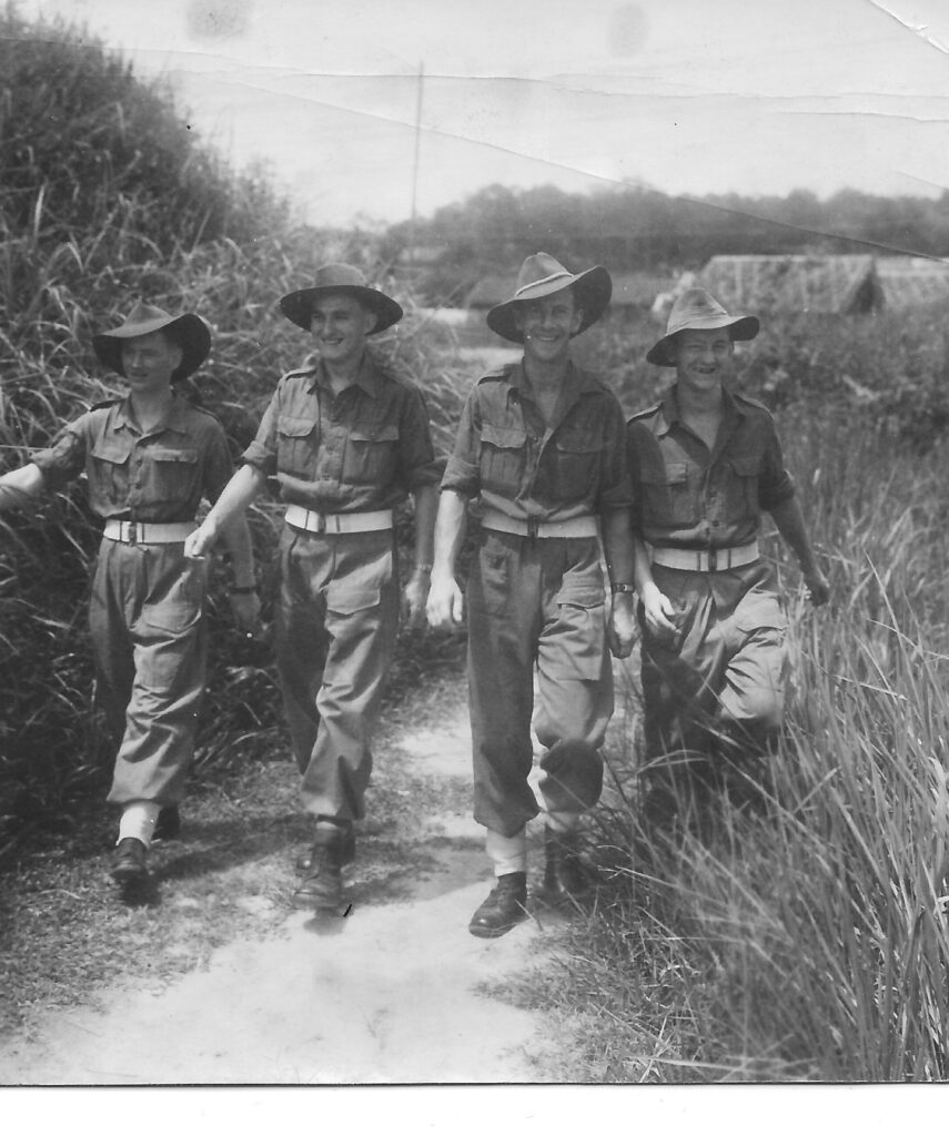 Photograph of Jim in Burma 1945 with 3 other soldiers walking along a track.