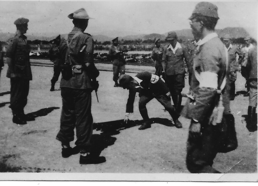 Photograph of Japanese surrender, Kuala Lumpar, September 1945. A group of Japanese soldier overseen by a British officer. One Japanese soldier wearing a white armband with a cross on it. bends down to pick something up.