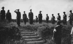 Photograph of Japanese surrender, Kuala Lumpar, September 1945. British Soldiers on a ridge above, the Officer salutes a Japanese officer below.